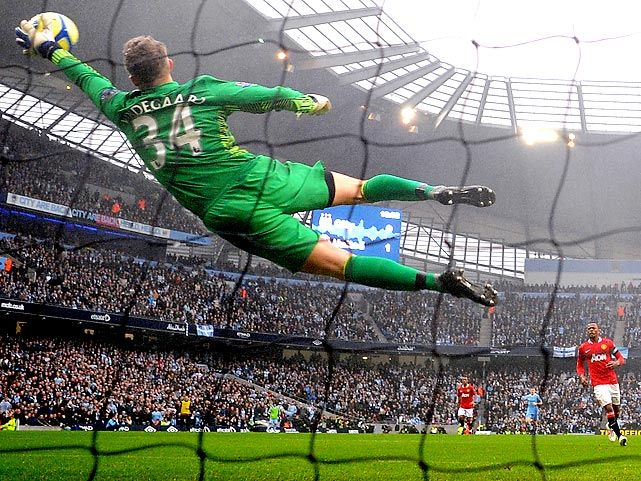 Manchester United goalie Anders Lindegaard stretches to save Manchester City forward Sergio Aguero's shot