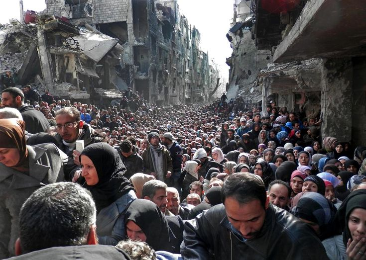 Jan. 31, 2014, and released by the UNRWA, shows residents of the besieged Palestinian camp of Yarmouk, queuing to receive food supplies, in Damascus, Syria