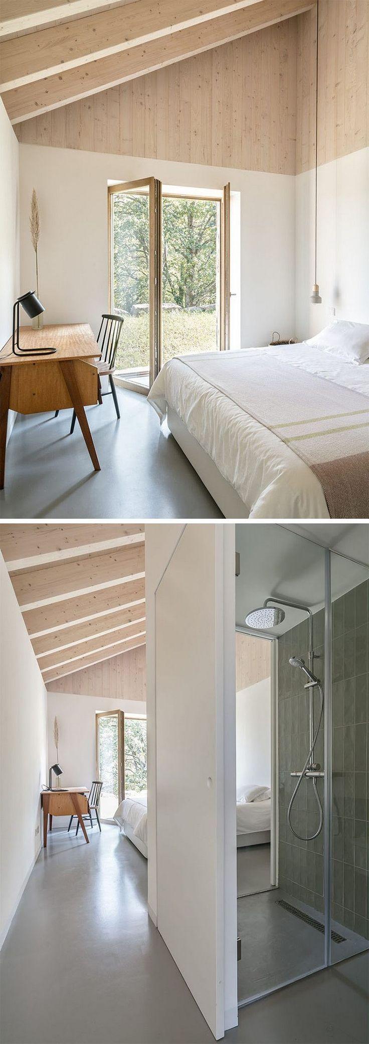 Raue Natursteinfassade in Kontrast zu weißen Wänden und hellem Holz im Innenraum