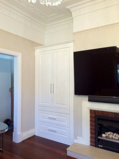 Beautiful custom feature storage either side of a fireplace Painted white finish to compliment the traditional style of the home