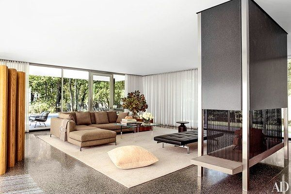 The living room is furnished with a B&B Italia sofa designed by Antonio Citterio, a Mies van der Rohe cocktail table by Knoll, a Poul Kjærholm daybed by Fritz Hansen, and a Knoll floor pillow; the curtain fabric is by Fabricut, and the fireplace was devised by Brad Dunning.