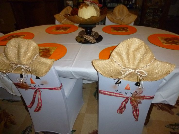 "I used inexpensive straw hats from the dollar store to top the chairs and help turn them into ""scarecrows"". The hats have a metal edge so it was no problem to bend the hats so that they would stay on the top of the chairs. Wire edged ribbon, fall leaves along with  duct tape features completed the look and took only minutes to apply.  I added cornucopia napkins and pine cones to the centerpiece."