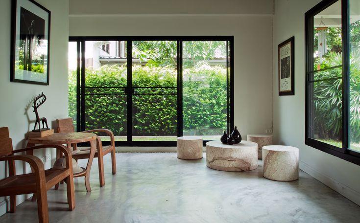 betonvloer in wit interieur met zwarte ramen