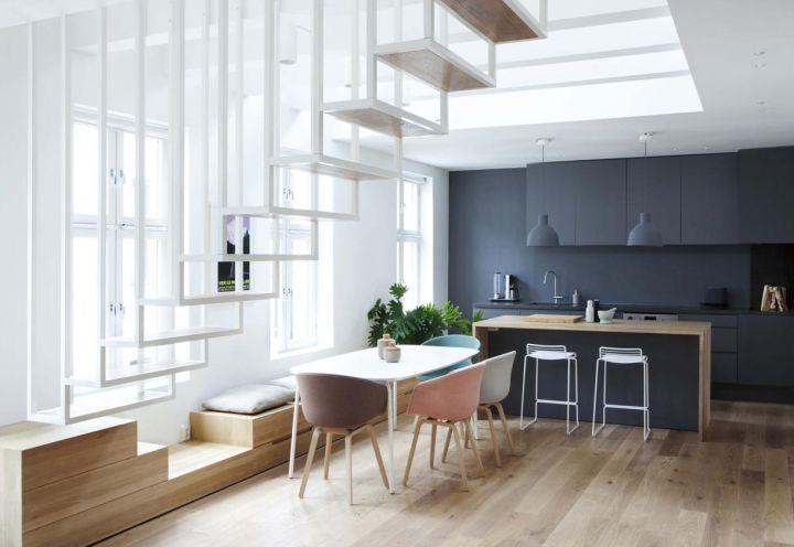 Una panca in legno con cuscini imbottiti corre lungo il perimetro delle finestre e definisce lo spazio. Attorno alla tavola da pranzo, le linee pulite e sinuose delle sedie Calligaris