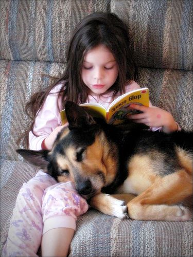 A little girl reads to her dog.