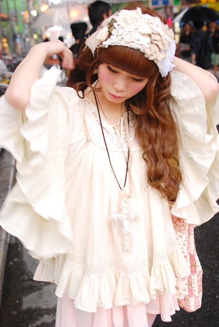 Cute, cult party kei: White headdress with flowers. White and pink poncho with frills. Necklace.