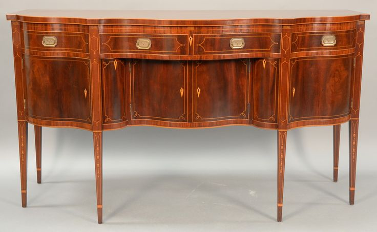 Margolis mahogany sideboard, Federal style with shaped top over conforming case with one center drawer flanked by two drawers over two center doors flanked by bottled drawers and two doors, all on square tapered legs. Realized Price $4,560.00