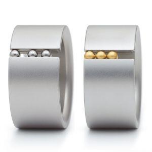 Niessing Abakus. »So viel Schwung wirkt ansteckend! Im breiten Ring aus Niessing Edelstahl bewegen sich drei Kugeln aus Gold, Stahl oder farbigen Synthesen. Purpurglühend, himmelblau, sonnengelb, magisch schimmernd, kühl glänzend perlen die Kugeln.