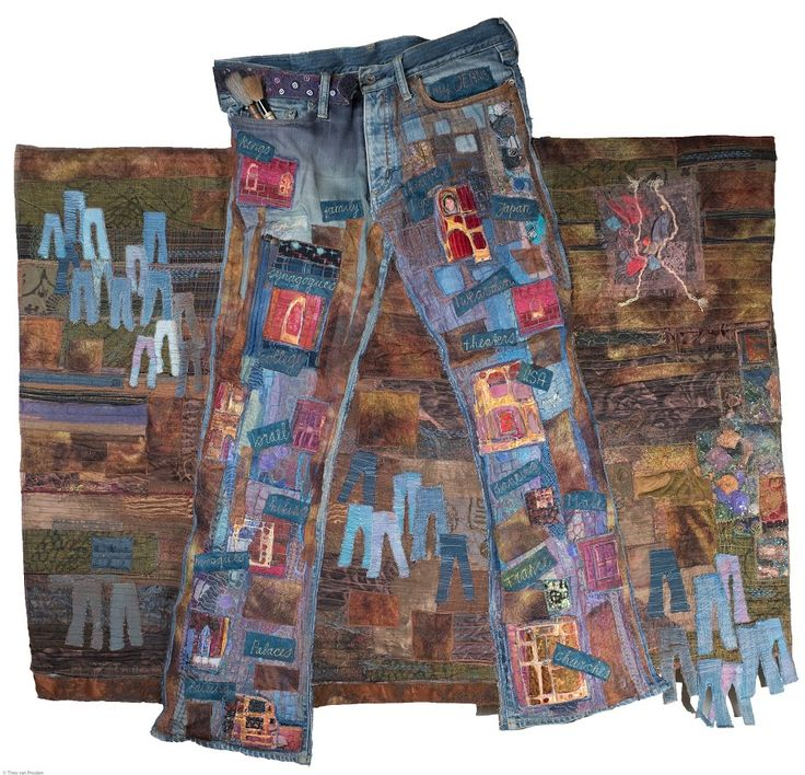 """Saskia Weishut-Snapper. Wherever I go...  In de Val d'Argent, Ste-Marie-aux-Mines, Frankrijk, won ik in 2006 de Quiltmania prijs van de internationale wedstrijd """"Fashion, reflection of an era"""" . Mijn inzending """"Wherever I go"""" toont een oude, bewerkte spijkerbroek van een zoon, waarop geborduurd de diverse landen en lokaties waar hij heen gaat, steeds gekleed in zijn jeans. Uit de broekzak steken twee sumi-e penselen en over de bruine achtergrond zijn kleine jeantjes verspreid."""