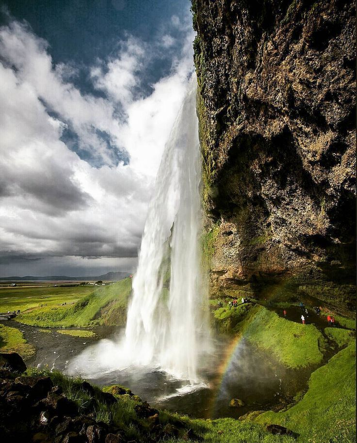 . Seljalandsfoss from behind Photograph by © (Rodrigo Oliveira). Seljalandsfoss is situated between Selfoss and Skogafoss, at Ring Road. This waterfall of the river Seljalandsáadrops 60 metres over the cliffs of the former coastline. #nature #iceland#waterfall#iceland_adventure