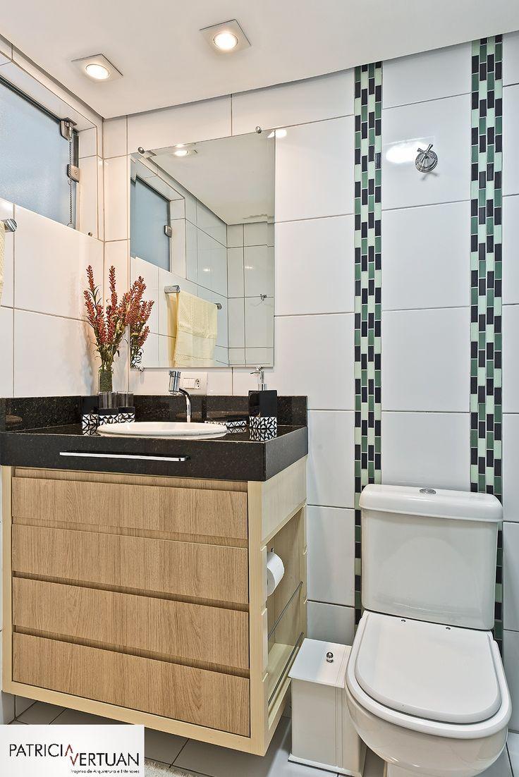Banheiro com revestimento em porcelanato branco e detalhe de inserto verde e azul  centralizado com vaso sanitário. A marcenaria foi desenhada especialmente para o projeto.