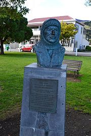 A bronze bust of FrankWorsley skipper, a man wearing a balaclava, the bust on a plinth in a park area with a backdrop of a park bench and buildings in the far distance