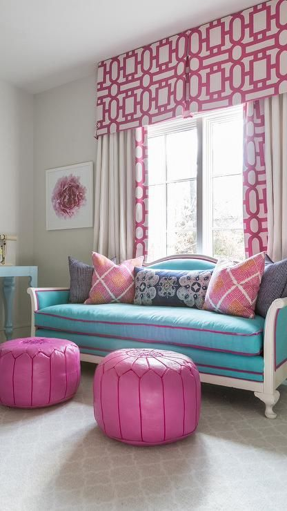 Pink and blue girl's room features a pair of hot pink Moroccan leather pouf placed in front of a turquoise French settee placed atop a gray trellis rug placed in front of a window dressed in pink geometric valances and curtains in Annette Tatum Candy Windowpane Fabric.
