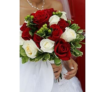 Hand tied bouquet of red Charlotte roses and ivory Vendella roses accented with variegated foliage and green hypericum berries.