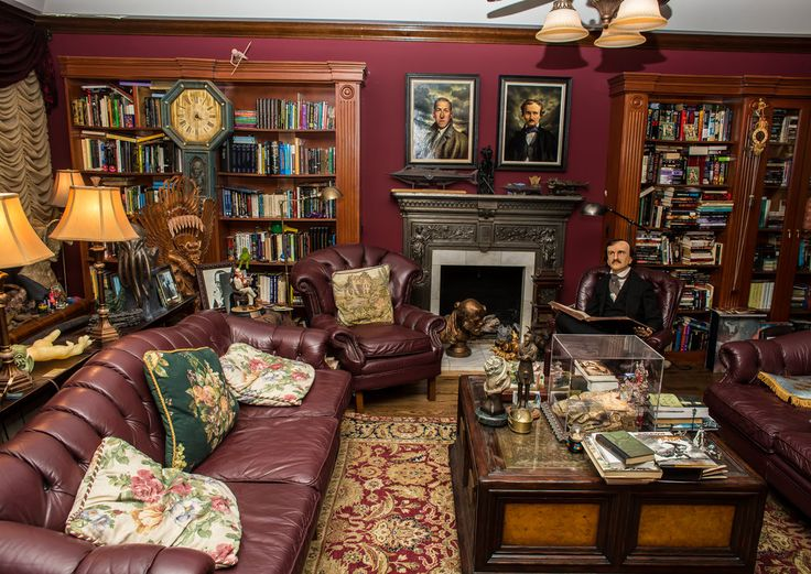 """Guillermo del Toro's Living Room """"Those two portraits are by a guy called Michael Deas. He's the guy who does all the U.S. mail commemorative stamps. He did James Dean and he did Poe, and I asked him to do a Poe and a Lovecraft.""""  Seated is Edgar Allan Poe, one of several life-size statues.  In the box on the coffee table is an ornate bed containing a skeleton, a reproduction of the captain's bed on the Disney """"Pirates of the Caribbean"""" theme park ride."""