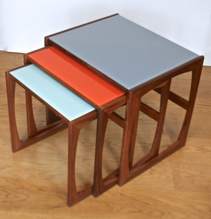 Our very popular up-cycled nest of GPlan tables in teak which we have restored then surfaced with coloured glass to make the tables more contemporary and more practical. Colours are a smoky blue, classic orange and a pastel blue. Condition is good and they are sound frames.