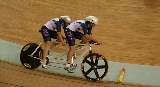 Dois atletas, usando capacete e uniforme dos Estados Unidos, pedalam na mesma…