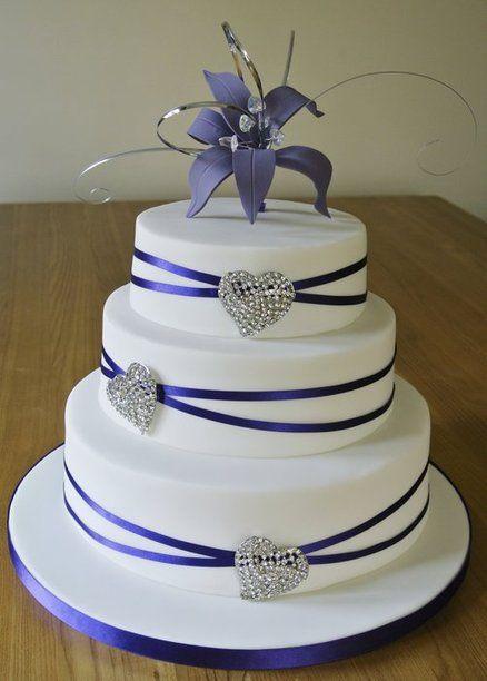 Torta fondo blanco de fondant con una cinta alrededor sujetada con broches de corazon y arriba flor azul igual que la cinta..