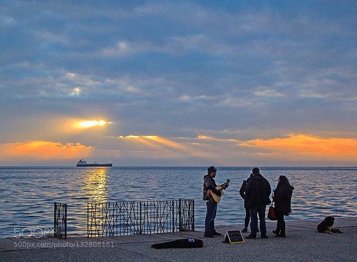 Golden hour at the waterfront Thessaloniki Sunset scene with a street musician chatting with passing-bters at the waterfront of Thessaloniki Greece....