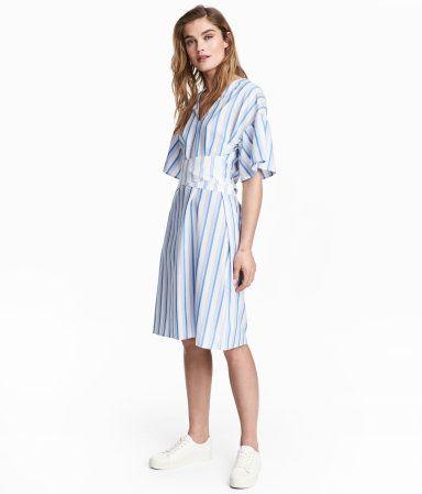 Weiß/Blau gestreift. Kurzes gestreiftes Kleid aus Viskosemischung. Das Kleid hat einen V-Ausschnitt, kurze weite Ärmel und einen breiten Bindegürtel in der