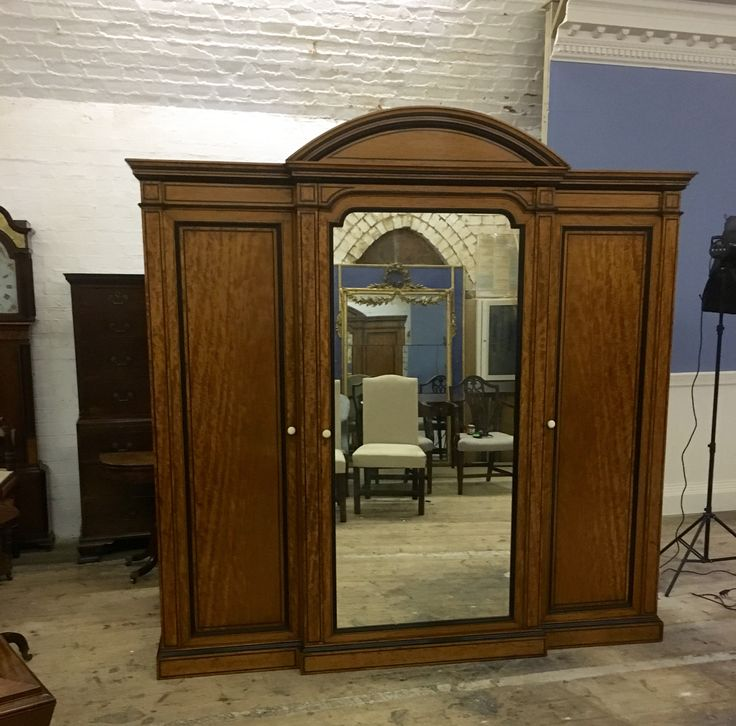 Antique satinwood with ebony mouldings. The triple 7ft wardrobe with mirrored central door , behind door is draws and trays ,either side full length hanging with draw a the bottom . part of a bedroom suite made around 1830   And designed by Owen jones