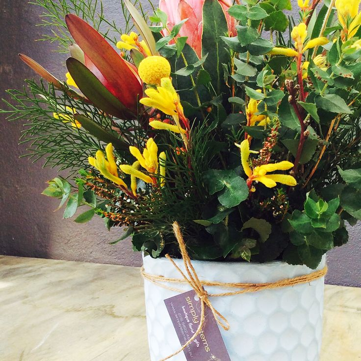"""Bright pops of colour from Kangaroo Paw and Billy Buttons contrasting the lush green foliage in this """"Have you Met Miss Jones"""" Blue Hive Pot."""