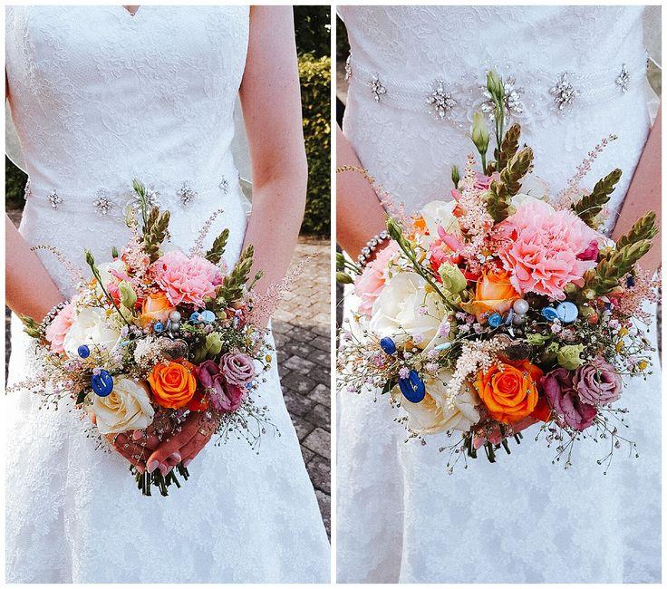 Ein Brautstrauß mit rosa Löwenmäulchen, rosa Nelken, rosa Astilbe, lila Schleierkraut, orange- und cremefarbene Rosen, Lysiantus, Kamille.