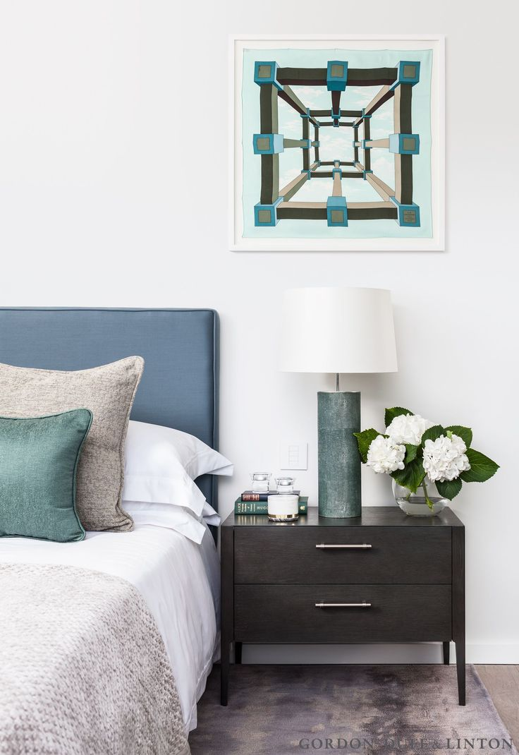 Bedroom with blue headboard, framed Hermes scarf and shagreen bedside lamp. The bedside table is a bespoke piece designed by Gordon-Duff & Linton. #GD&LBespokeFurniture