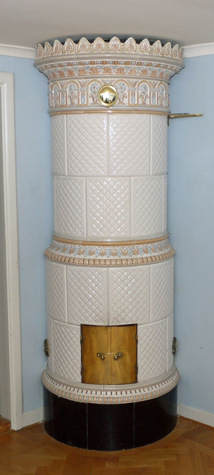 White tiled stove with relief tiles and pastel coloured decorations and a dark brown plinth, ca 1900. Height 215 cm.