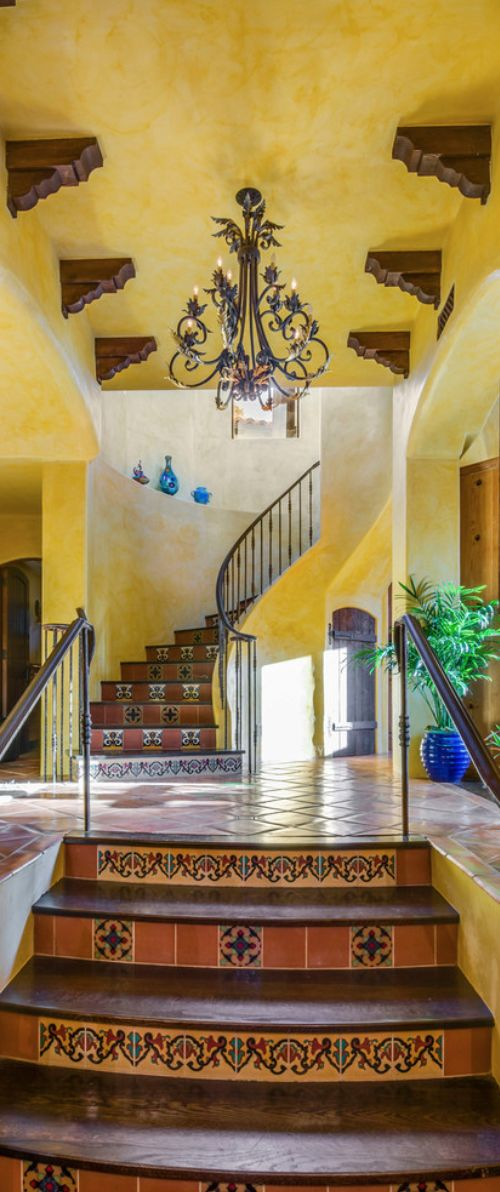 ~Delectable Spanish style. This house is gorgeous! Love the wall color; though I'd choose a warmer tone. Love the tile floors, stair risers and railing. This, coupled with the blue vase vignette on the wall near the staircase. I would switch the center light fixture for a Spanish-style chandelier, potted urns full of Boston ferns, English ivys and parlor palms dispersed throughout the house. ~