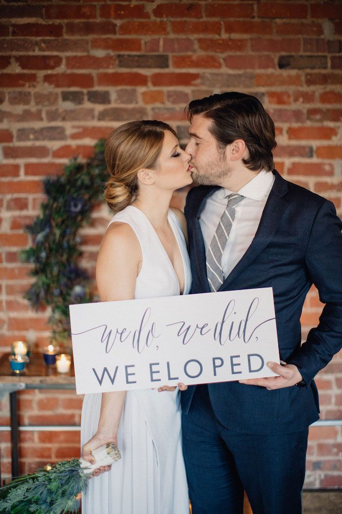 "Bride and groom holding ""we eloped"" sign. Loft elopement on @intimatewedding with photography by @clarencephoto  #elopement"