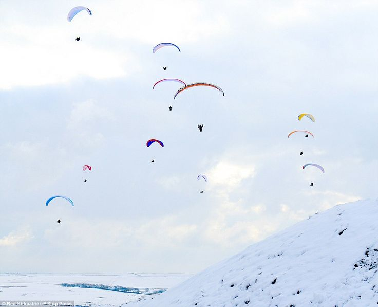 Cool activity: Paragliders take to the skies today over Mam Tor, high above Castleton in the Derbyshire Peak District