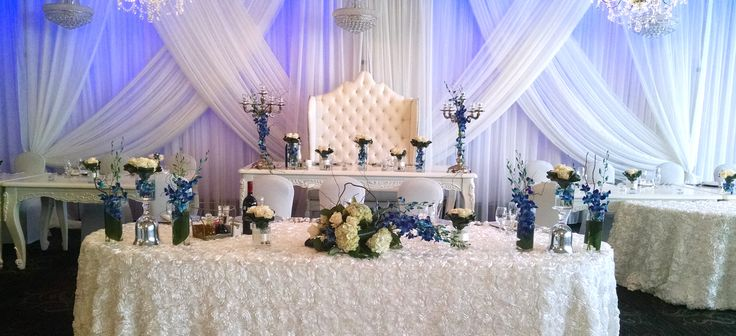 Blue dendrpbium orchids spread on a headtable with white roses