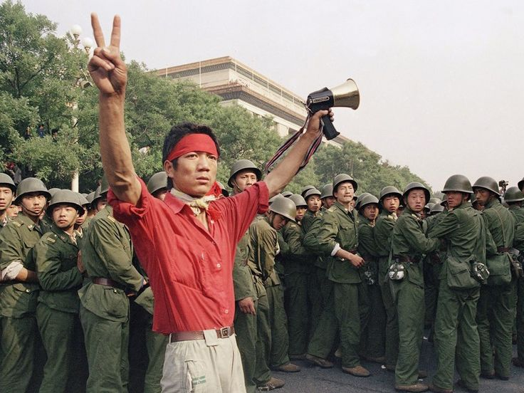 A student pro-democracy protester flashes victory signs to the crowd as People's Liberation Army troops withdraw on the west side of the Great Hall of the People near Tiananmen Square on Saturday, June 3, 1989 in Beijing. (AP Photo/Mark Avery)
