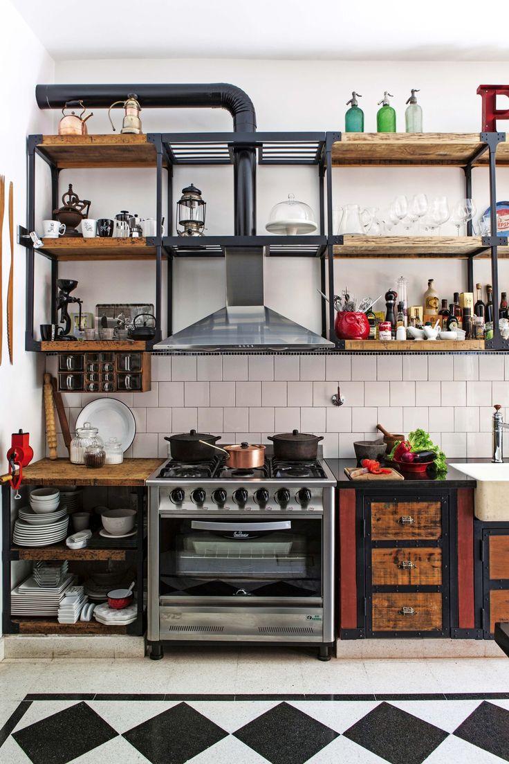 Cocina rústica con muebles de maderas recuperadas y puertas recicladas (Horacio Manzione), y mesada con doble mármol negro.