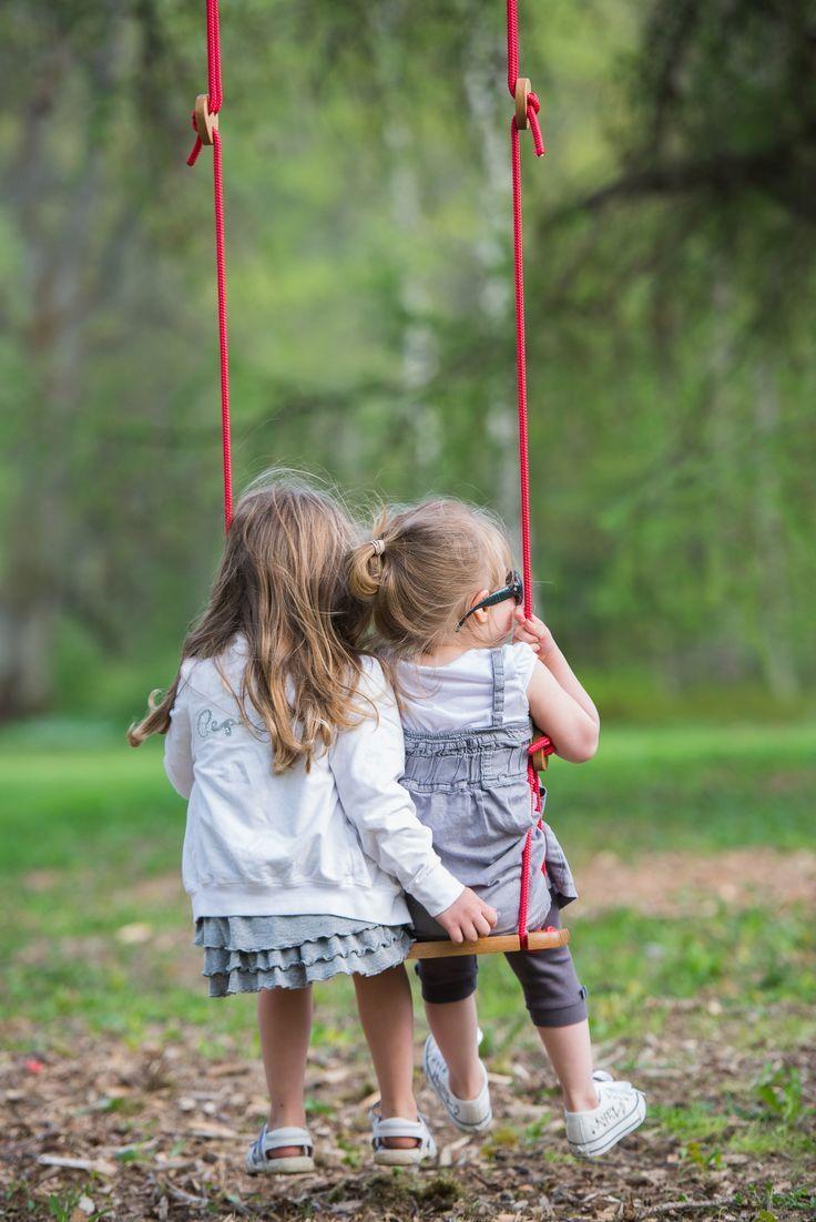 .Two little girls in a swing; friends; play