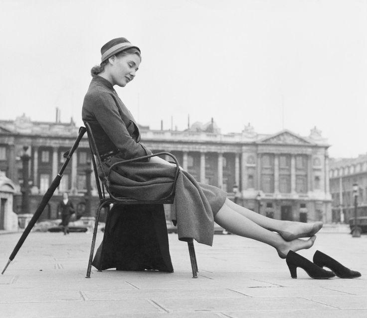 Kvinna i klänning och hatt sitter på en stol vid ett torg och har tagit av sig sina pumps. Mot stolsryggen står ett paraply lutat. 1950-55. Foto:  Gösta Glase. CC-BY.