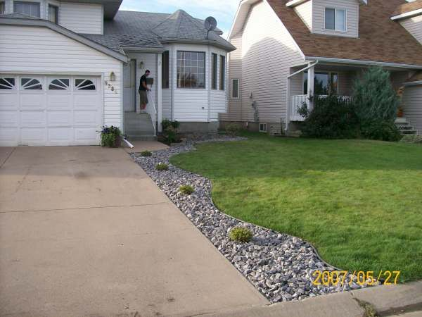 Winterkill in northern climates from snow, ice and salt down the edge of a driveway can be a losing battle. Installing edging and rock or mulch beds has become a very popular and effective way to deal with this issue.  Picture compliments of Dream-yard.