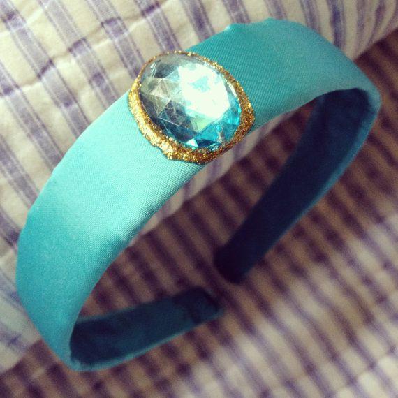 • Teal satin fabric headband. • Attached jewel with gold painted accent. • 1 inch shatterproof plastic headband. • Aladdin, Princess Jasmine