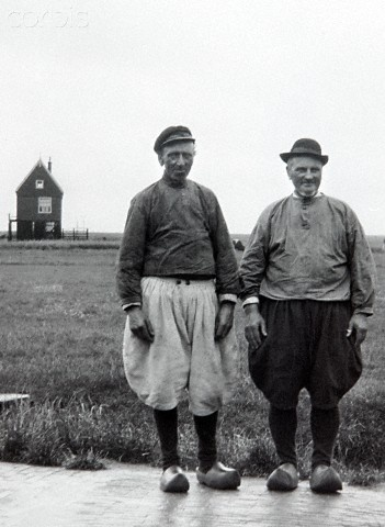 Local men in Marken, The Netherlands, ca. 1910.  Two traditionally dressed men stand for a tourist photograph in The Netherlands. #NoordHolland #Marken