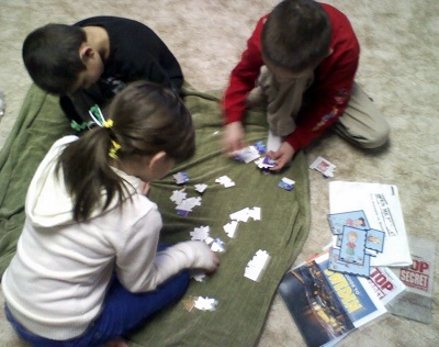 Puzzles are a great way to get your children working and playing together. Give them a job where 1 gathers the border pieces and one the inside pieces and if there are young ones, give them the job of flipping each piece over. Once that is done sort for the corners, the words...etc. Keep them helping each other and keep encouraging them!