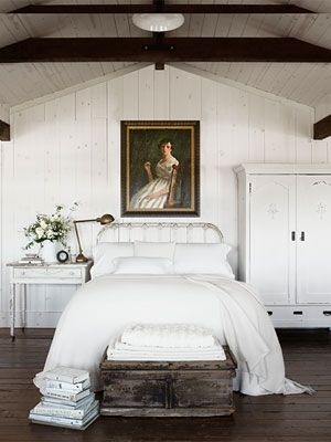 Rustic White Railroad trestles were installed as beams in this rustic bedroom. A flea market oil portrait watches over the antique iron bed, covered with Pottery Barn's fisherman-knit blanket.    Read more: Bedroom Design Ideas - Guide to Bedroom Design - Country Living.