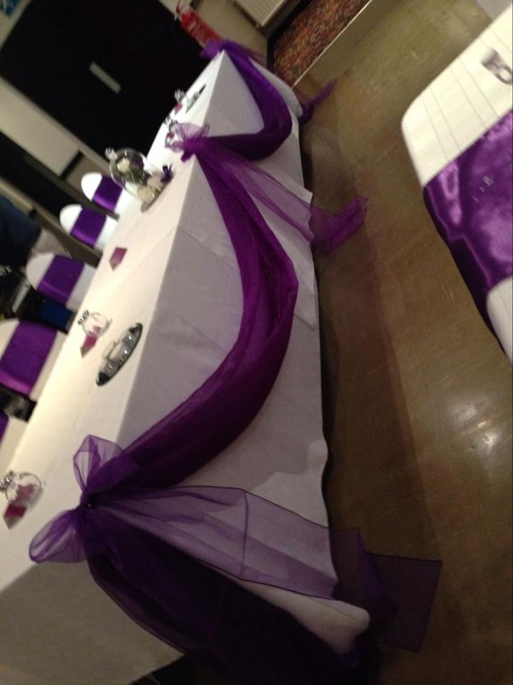 Cadbury Purple satin sashes with white spandex chaircovers. Enfield cricket club, Accrington, Lancashire. Wedding party decorations. Top table swag.