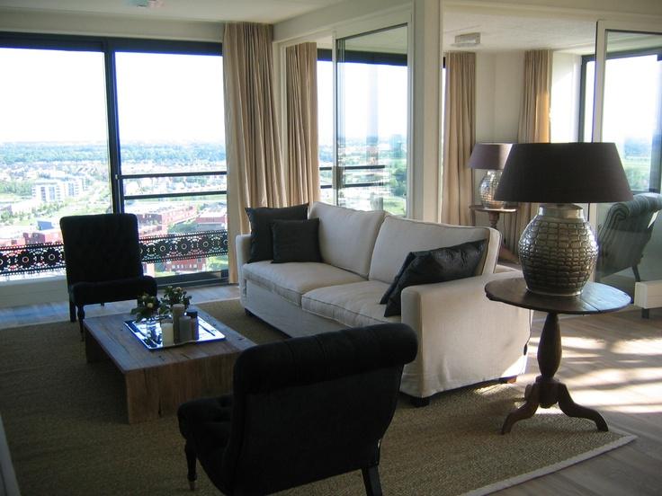 woonkamer met lichte bank zwarte stoelen zonder armleuning sisal