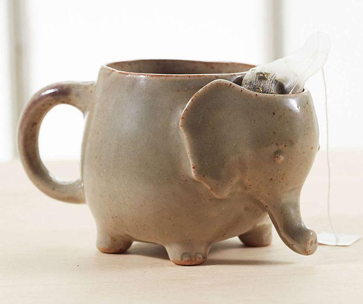 A handmade stoneware tea mug shaped like a cute little elephant with a handy compartment to stash a tea bag after brewing.