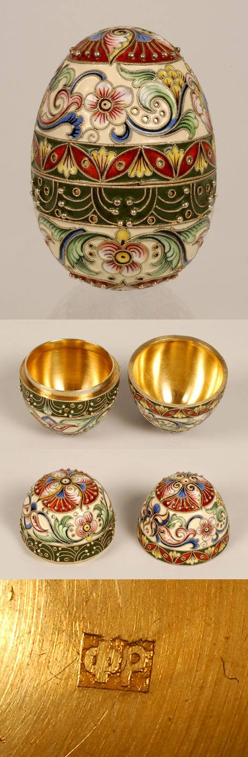 A Russian gilded and shaded cloisonne enamel egg by Feodor Ruckert, Moscow, decorated with bands of red and green enamel at the opening as well as shaded foliage against cream grounds