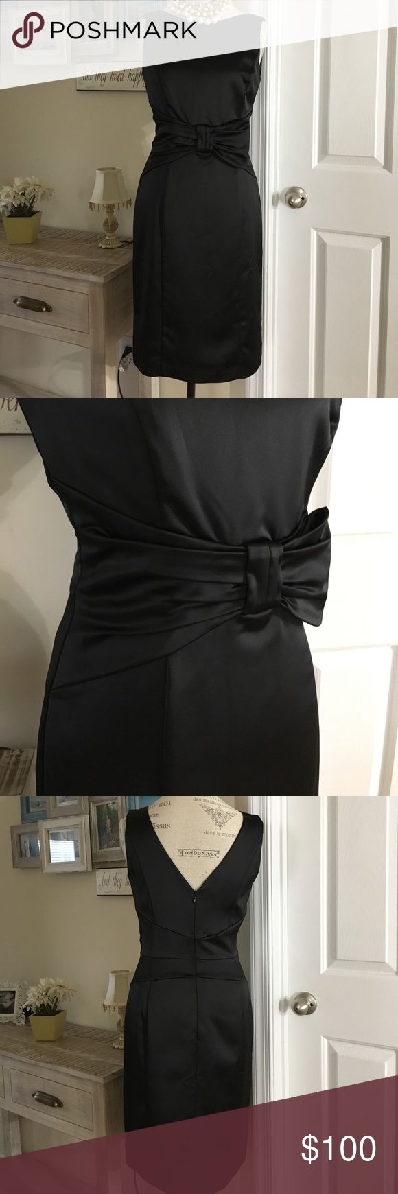 White House Black Market Black Satin Bow Dress 4 This dress is beautiful, stylish and very sophisticated. A must have dress! It is solid black, double lined and zips up the back. The material looks like a satin material but it's actually made out of polyester. There is a gorgeous bow detail on the front which I love. It adds so much character to this dress. It's available in a size 4 and the fit is very true to size. The bottom hem in the back has a small slit which is still sewn together as…
