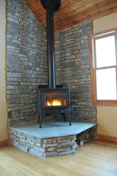 This is a great corner woodburning stove with a nice roaring fire. Note the wood storage on the right side under the hearth.