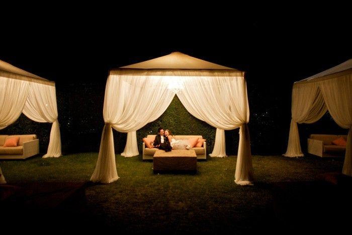 Se você quer um lounge romântico em sua festa, escolha um local mais afastado da bagunça e use tendas para tornar o ambiente mais íntimo e envolvente.