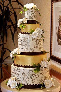 Gold, brown and olive was the sophisticated color palette for this amazing wedding cake. This five tire wedding cake is decorated with large white rose, gold scroll work and gold cake icing.